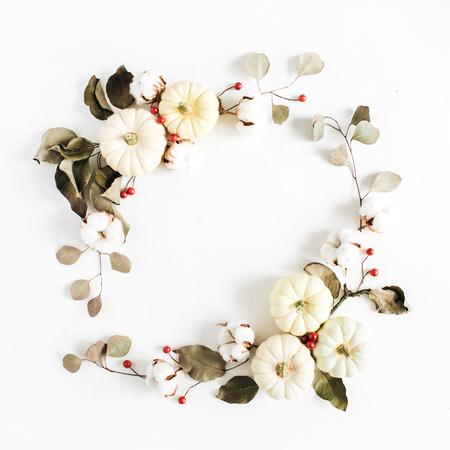 Marco de guirnalda hecha de calabazas blancas, bayas rojas, bolas de algodón y ramas de eucalipto sobre fondo blanco. Endecha plana, vista superior Composición de Navidad. Foto de archivo - 89701241