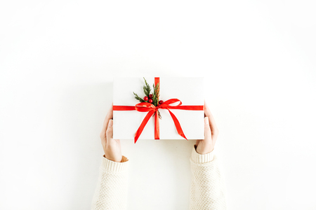 Christmas concept. Female hands holding gift box. Flat lay, top view.