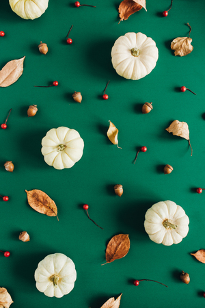 White pumpkins, red berries and eucalyptus branches on green background. Flat lay, top view. Christmas background.
