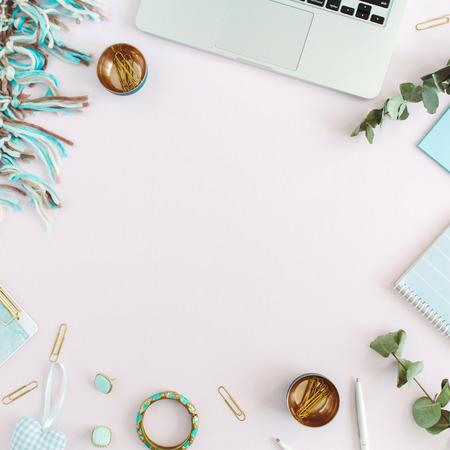 Werkruimtekader van laptop, plaid, klembord, accessoires op roze achtergrond. Plat lag, bovenaanzicht vrouwen bedrijfsconcept.