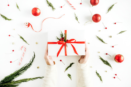 Christmas gift box in woman hands on decorated background. Flat lay, top view holiday composition.