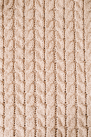 Beige knitted wool texture pattern background.