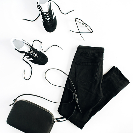 Trendy fashion black styled woman clothes and accessories look on white background. Flat lay, top view.