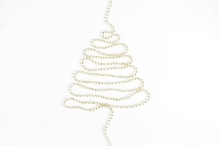 白い背景に金色のボーブルで作られたクリスマスツリー。フラットレイ、トップビューホリデーコンセプト。