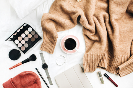 Female fashion look with stylish clothes and accessories. Lifestyle flat lay, top view composition with sweater, cosmetics and coffee.