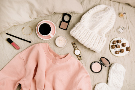 Female fashion clothes and accessories. Lifestyle flat lay, top view composition with sweatshirt, cosmetics and coffee.