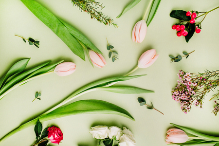 Flowers pattern made of pink tulips, roses, hypericum flower on green background. Flat lay, top view. Stock Photo
