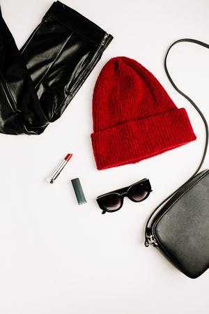 Female fashion clothes and accessories on white background. Red hat, black purse, sunglasses, lipstick and leggings. Flat lay, top view look. Stock Photo