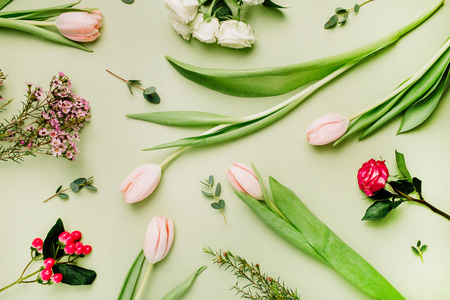 Flowers pattern made of pink tulips, roses, hypericum flower on green background. Flat lay, top view spring floral concept.