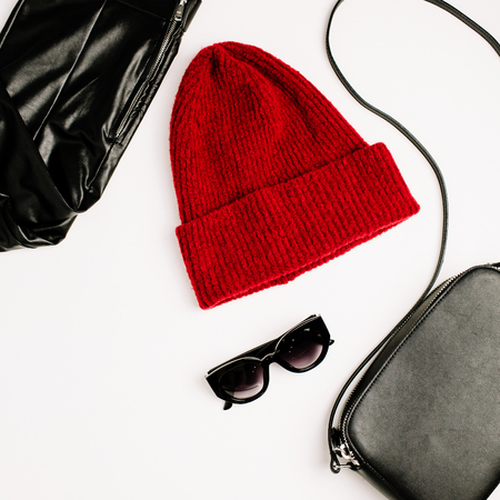 Female fashion clothes and accessories on white background. Red hat, black purse, sunglasses and leggings. Flat lay, top view lifestyle look. Stock Photo