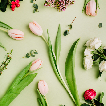Flowers pattern of tulips, roses, hypericum flower on green background. Flat lay, top view spring concept. Stock Photo