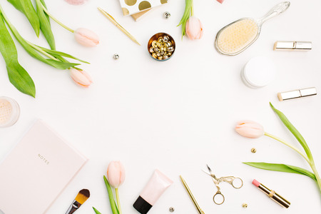 Frame of pink tulip flowers, accessories and cosmetics. Female home office desk mockup. Flatlay, top view blog hero header background. Stok Fotoğraf - 96819544