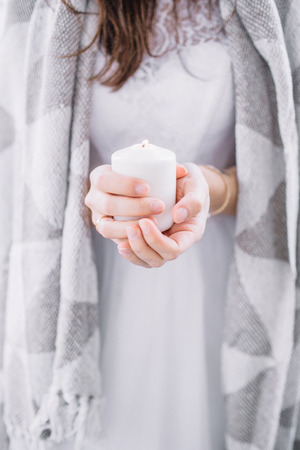 Young woman wrapped in grey blanket with candle in hands.