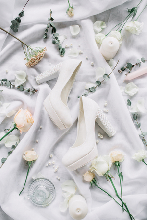 Wedding stylish composition with high heel shoes, eucalyptus branches, rose flowers on white textile background. Flat lay, top view festive wedding fashion concept. Stock Photo