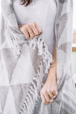 Young woman wrapped in grey blanket.