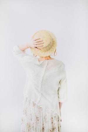 白い背景に麦わら帽子をかぶった若い女性の背中。 写真素材