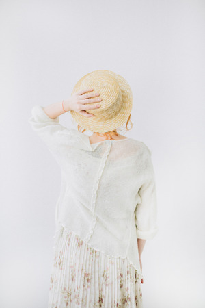Back of young woman in straw hat on white background.