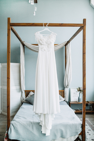 Beautiful white wedding bridal dress in front of bed. Stock Photo