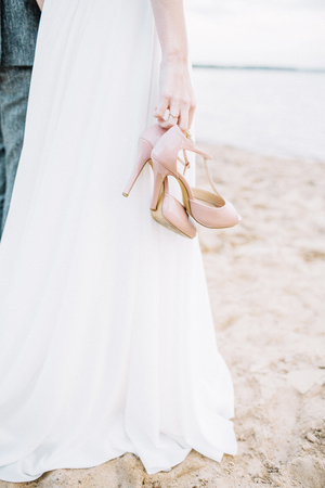 High heel shoes in young woman hands on beach. Imagens