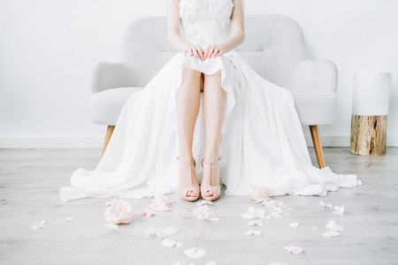 Young bride legs in pink high heel shoes and pink flower petals. Festive wedding fashion concept.
