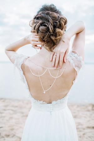 Young pretty woman in elegant dress. Back view wedding fashion background.
