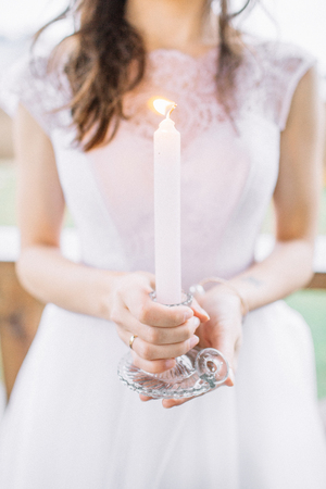 Young woman in evening dress holding candle. Wedding festive concept. 스톡 콘텐츠