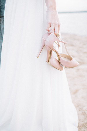 Young woman on beach holding high heel shoes. Imagens