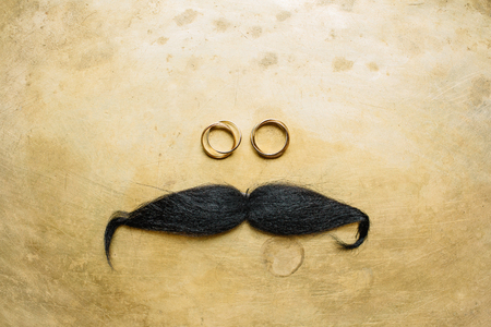 Wedding rings and mustache on golden background. Flat lay, top view.