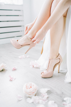 Young woman puts on pink high heel shoes in bright room with rose flower buds. Wedding bridal fashion concept.