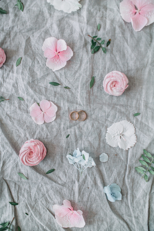 Festive wedding background with pink flower buds, eucalyptus branches, bridal rings, sweets on grey blanket. Flat lay, top view. Stock Photo
