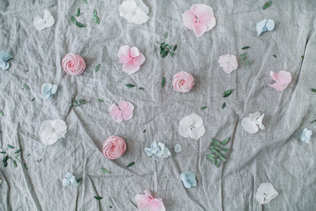Festive background with pink flower buds, eucalyptus branches, sweets on grey blanket. Flat lay, top view.