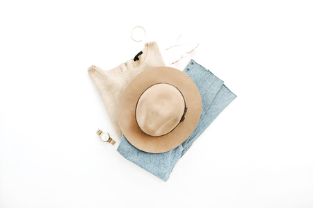Woman stylish fashion clothes and accessory set on white background. Hat, boyfriend jeans, sweater, sunglasses, bracelet and watch on white background. Flat lay, top view. Banco de Imagens
