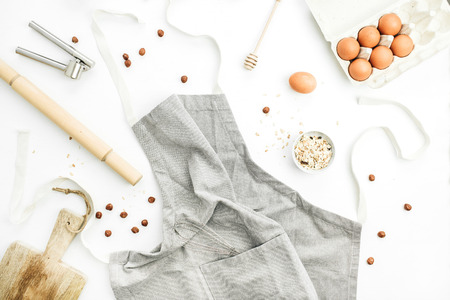 Healthy food ingredients: eggs, hazelnut, cereals, apron. Cooking concept. Flat lay, top view.
