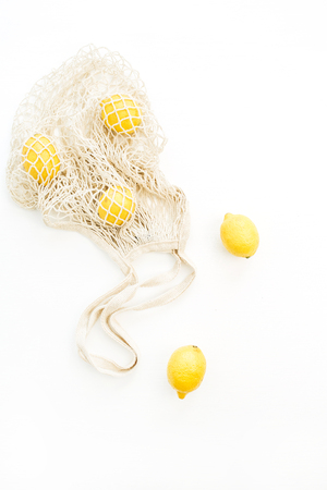 Fresh raw lemons in string bag on white background. Flat lay, top view summer concept. Zdjęcie Seryjne - 101589587