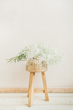 White gypsophila flower bouquet on wood stool at pale pastel beige background. Minimal lifestyle concept. Stock Photo