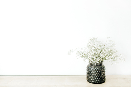 White gypsophila flowers bouquet in flowerpot at white background. Minimal floral concept.