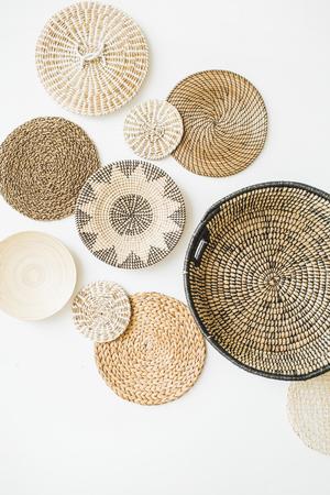 Decorative straw plates on white wall. Modern minimal home interior design.