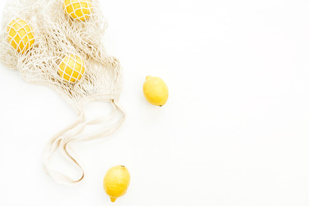 Fresh raw lemons in string bag on white background. Flat lay, top view summer concept.