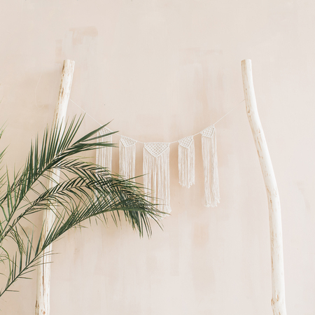 Minimal home interior design. Tropical palm branches and boho decoration at pastel beige wall. Stock Photo