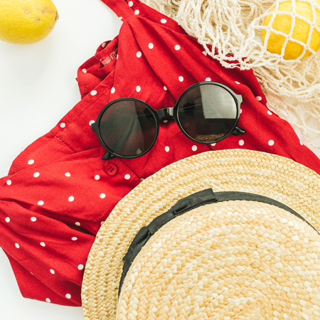 Summer female fashion stylish composition. Red dress, straw, string bag, sunglasses and lemons on white background. Flat lay, top view. Stock Photo