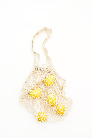 Fresh raw lemons in string bag. Flat lay, top view summer concept.
