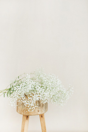 White gypsophila flowers bouquet on wooden backless stool at pale pastel beige background. Minimal festive holiday concept.