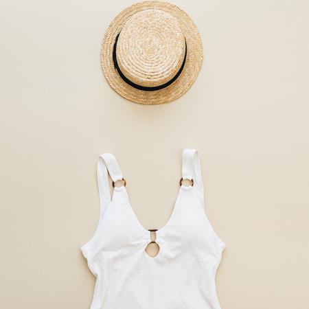 Flat lay summer fashion composition. Women's swimsuit, straw on pastel beige background. Flat lay, top view minimal beach concept. Standard-Bild