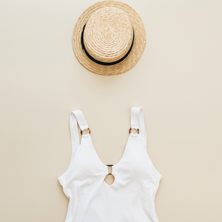 Flat lay summer fashion composition. Womens swimsuit, straw on pastel beige background. Flat lay, top view minimal beach concept. Banco de Imagens