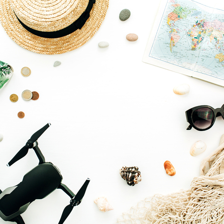 Summer travel concept. Frame with space for text of world map, drone, straw, sunglasses, coins on white background. Flat lay, top view traveler blogger mock up concept. Stockfoto