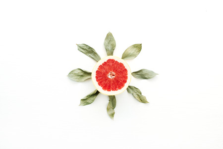 Sun symbol made of sliced grapefruit and leaves. Flat lay, top view summer concept.