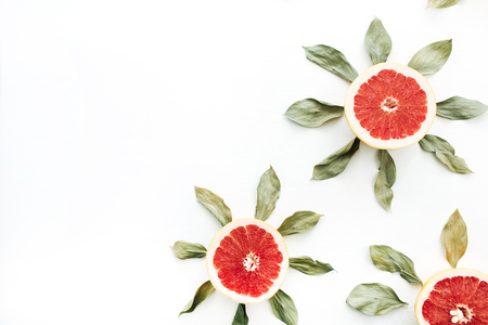 Sun symbol pattern made of sliced grapefruit and leaves. Flat lay, top view summer creative concept.