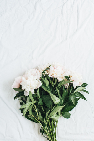 Flat lay, top view of white peonies flower bouquet on white blanket background. Minimal summer floral concept. Stock Photo