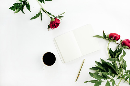 Minimal home office desk with notebook, coffee and peony flowers on white background. Flat lay, top view workspace concept.