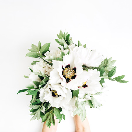 Woman hands holding white peonies bouquet on white background. Flat lay, top view. Floral composition.
